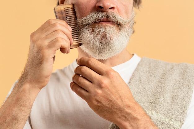 Homem mais velho com toalha, penteando a barba