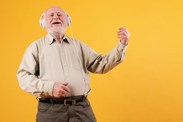Homem mais velho de ângulo baixo tocando quitar imaginário