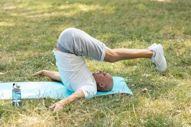 Homem mais velho, duradouro alongamento no tapete de ioga