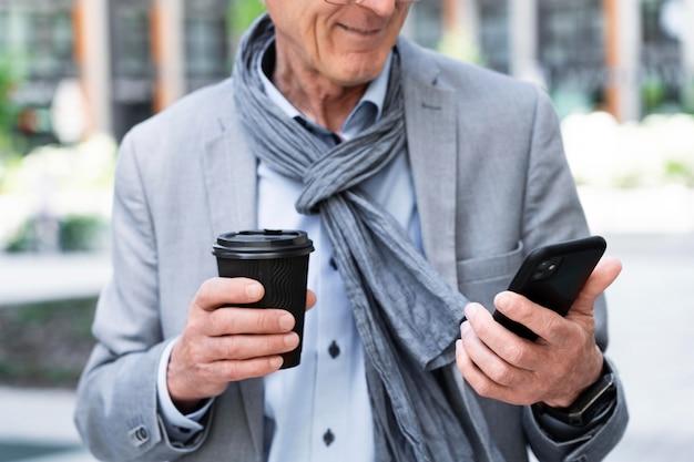 Homem mais velho elegante na cidade usando smartphone enquanto toma café