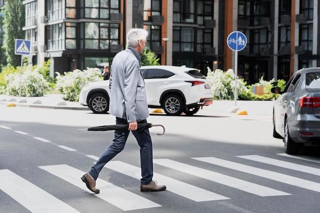 Homem mais velho estiloso na cidade, atravessando a rua segurando um guarda-chuva
