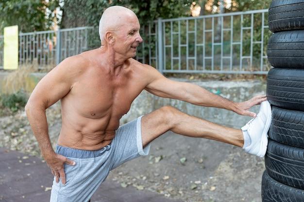 Homem mais velho musculoso, estendendo-se ao ar livre
