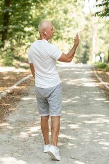 Homem mais velho na parte de trás, olhando para o celular