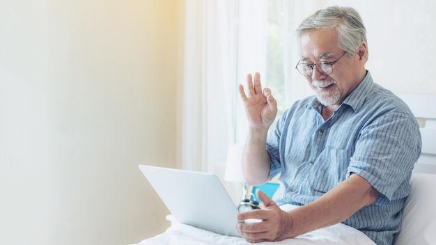 Homem mais velho usando uma chamada facetime de computador portátil para parentes