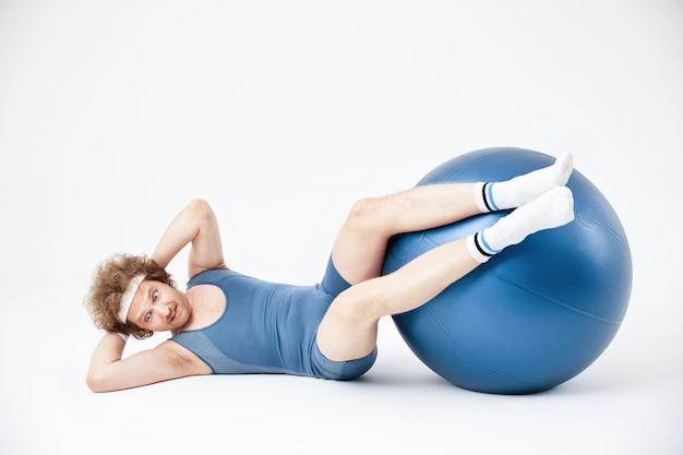 Homem malhando abs com pernas na bola de exercício