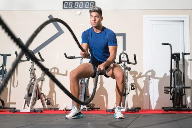 Homem malhando com corda na academia de ginástica e treinamento funcional