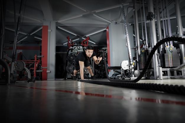 Homem malhando com cordas de batalha na academia, treinamento funcional, treinamento físico esportivo, conceito de pessoas de estilo de vida