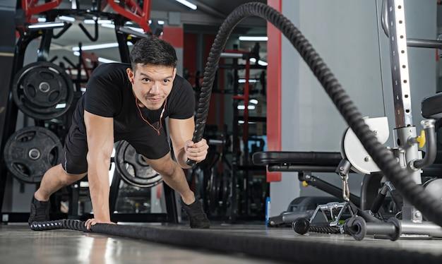 Homem malhando com cordas de batalha na academia
