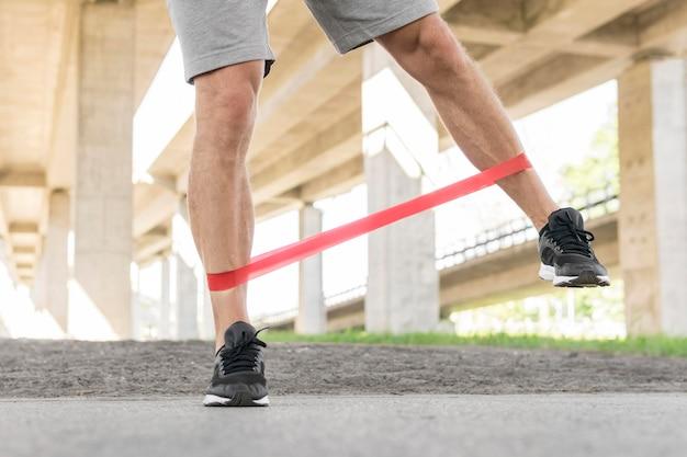 Homem malhando com uma faixa de alongamento nas pernas