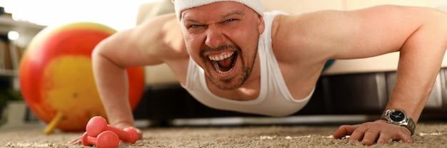 Homem malhando em casa, treinando esportivo masculino