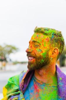 Homem manchado de tinta em pó com bandeira de arco-íris, sorrindo na rua