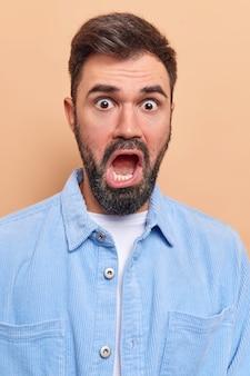 Homem mantém a boca bem aberta parece envergonhado com a câmera ouve notícia inesperada e surpreendente usa camisa de veludo azul olha com indignação