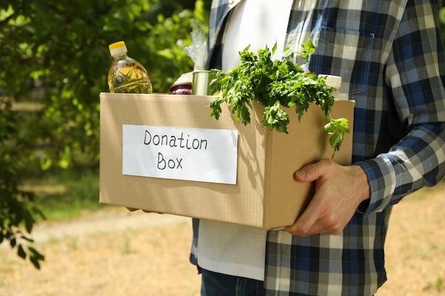 Homem mantém a caixa de papel de doação ao ar livre. voluntário