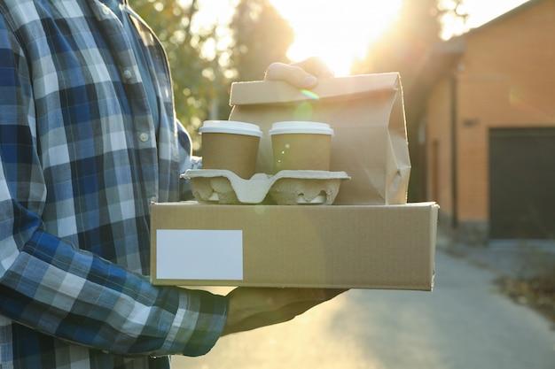 Homem mantém a caixa em branco, copos de café e pacote de papel ao ar livre. entrega