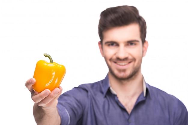 Homem mantém a pimenta amarela na mão e sorri.