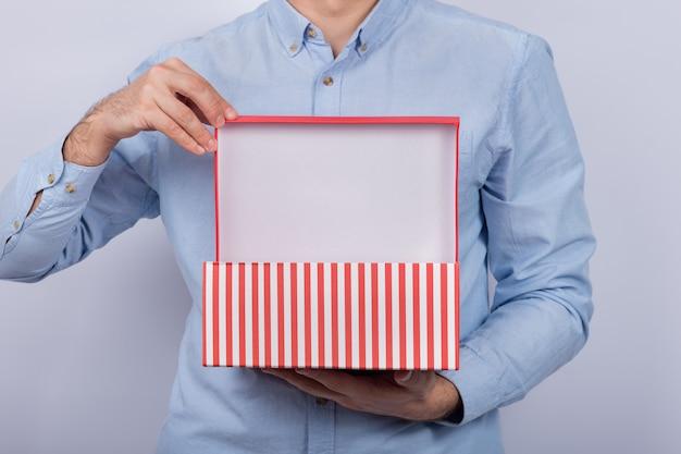Homem mantém aberta a caixa festiva. caixa de presente nas mãos dos homens. vista frontal