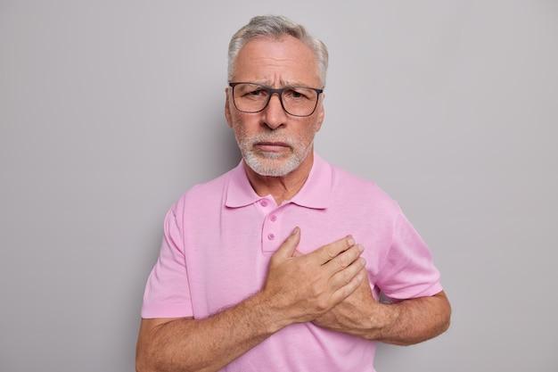 Homem mantém as mãos pressionadas contra o peito tem problemas cardiovasculares ataque cardíaco derrame súbito precisa visitar cardiologista estandes internos