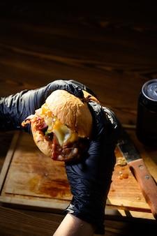 Homem mantém pronto saboroso hambúrguer nas mãos em luvas pretas.