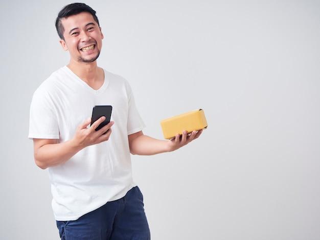 Homem mantém smartphone e caixa de encomendas
