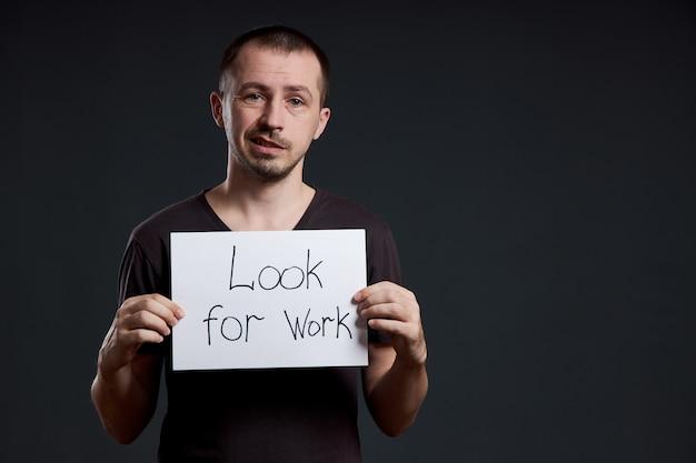 Homem mantém um sinal com as palavras à procura de trabalho, desemprego e crise