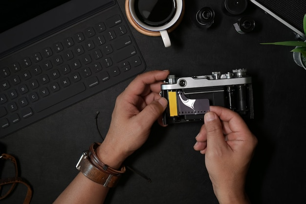 Homem, mão, carregando, película, 35mm, ligado, câmera vintage, em, couro escuro, escrivaninha