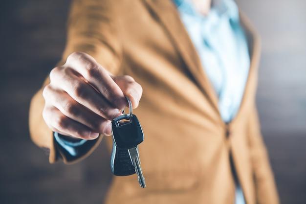 Homem mão chave do carro em fundo escuro