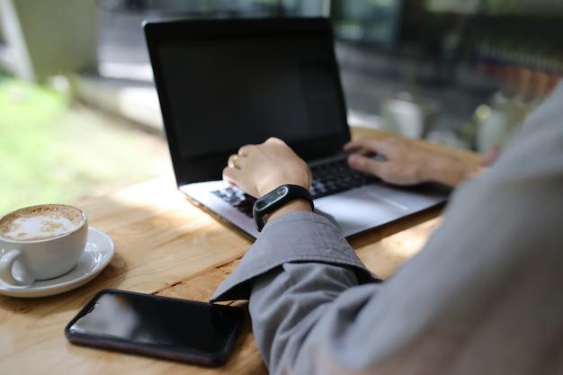 Homem mão e dedo digitando teclado do laptop na mesa de madeira com telefone e xícara de café, relógio inteligente