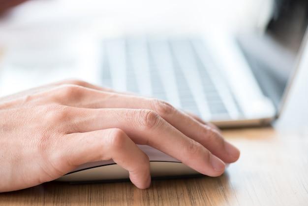 Homem mão no mouse usando um laptop