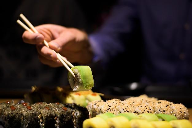 Homem mãos comendo sushi rolos com palitos de madeira