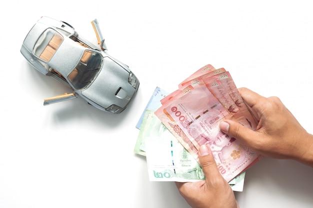 Homem mãos contando notas tailandesas com modelo de carro em fundo branco