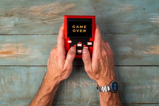 Homem mãos segurando console retrô jogando videogame