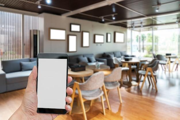 Homem, mãos, segurando, em branco, tela, um, smartphone, e, obscurecido, sala de estar, fundo