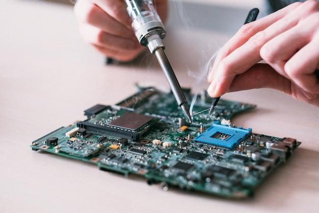 Homem mãos soldando componentes eletrônicos na placa do pc