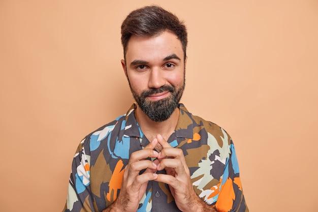 Homem maquina algo steepls dedos tem uma expressão astuta o mal planeja pensa em smth desonesto usa uma camisa casual colorida isolada em um estúdio bege