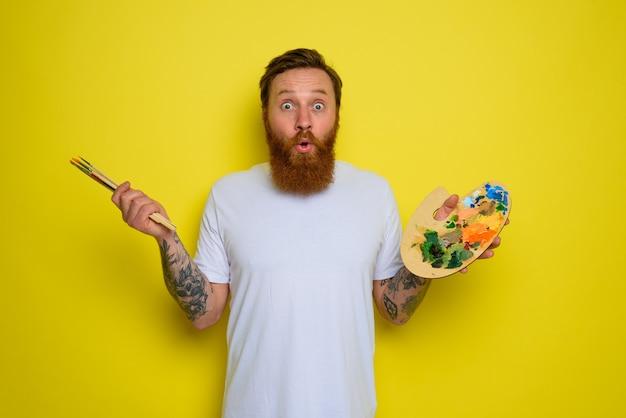 Homem maravilhado com barba e tatuagem está pronto para desenhar com pincéis