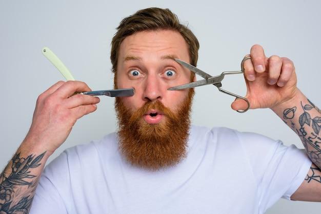 Homem maravilhado com tesoura e lâmina está pronto para cortar a barba