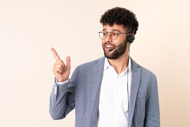 Homem marroquino de telemarketing trabalhando com um fone de ouvido isolado em uma parede bege com a intenção de perceber a solução enquanto levanta um dedo