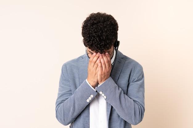 Homem marroquino do telemarketing trabalhando com fone de ouvido isolado em um fundo bege com expressão de cansaço e enjoo