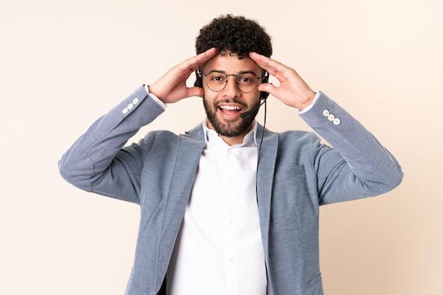 Homem marroquino do telemarketing trabalhando com um fone de ouvido isolado em um fundo bege com expressão de surpresa