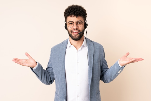 Homem marroquino do telemarketing trabalhando com um fone de ouvido isolado em uma parede bege com expressão facial chocada