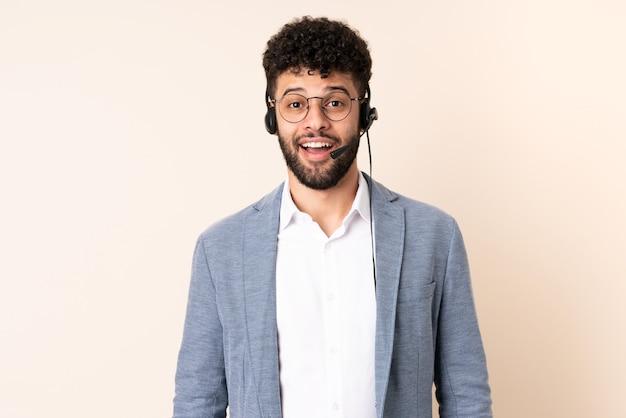 Homem marroquino do telemarketing trabalhando com um fone de ouvido isolado em uma parede bege com expressão facial surpresa