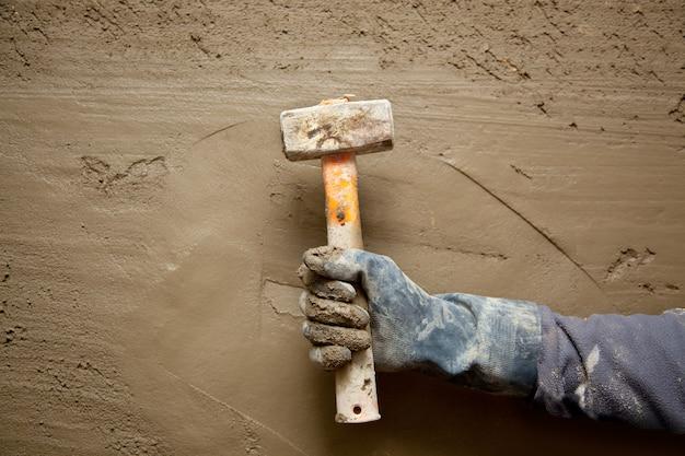 Homem martelo com luvas em cimento grunge