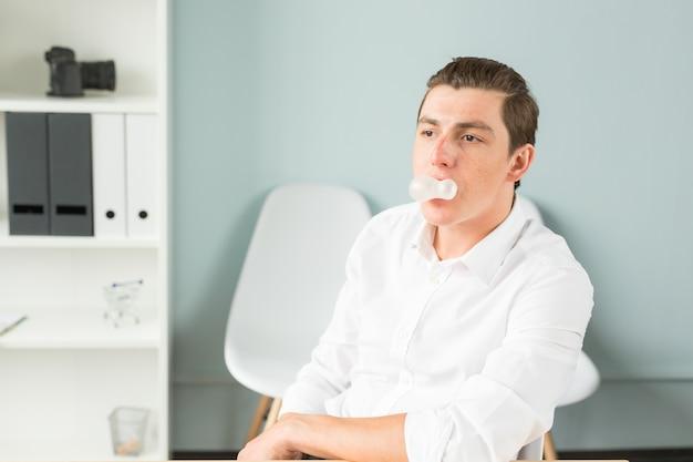 Homem mascando chiclete no escritório