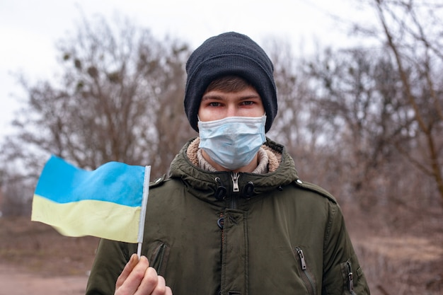 Homem mascarado doente com bandeira da ucrânia. surto de coronavírus na ucrânia. pandemia covid-2019