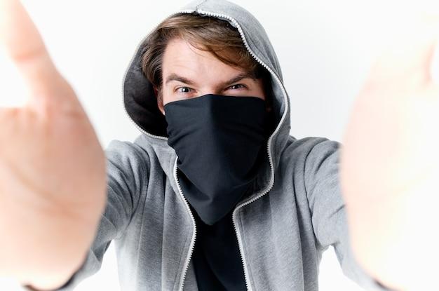 Homem mascarado na máscara com fundo isolado de roubo de emoções de capuz. foto de alta qualidade