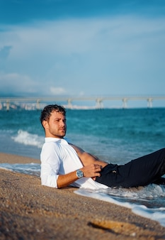 Homem masculino relaxando na praia molhada à noite