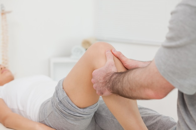 Homem massageando a perna de uma mulher