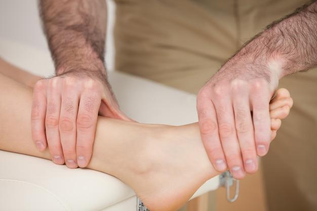 Homem massageando o pé de uma mulher
