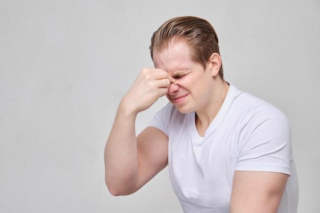 Homem massageia a ponte do nariz de dor dolorida.