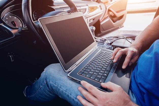 Homem mecânico com laptop, fazendo diagnósticos de carro no serviço de auto